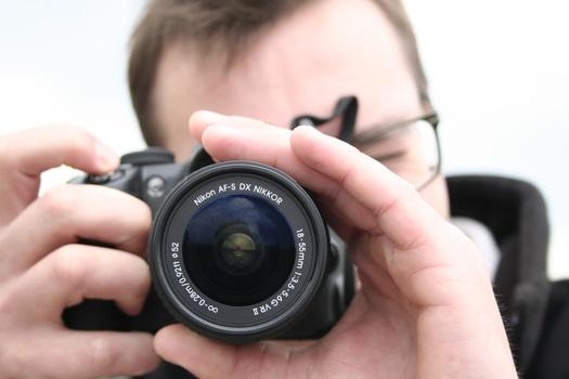 Mann schaut durch Foto und stelle Objektiv ein