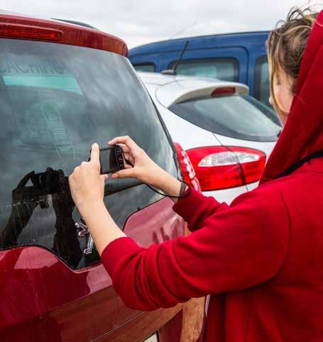 Was ist Geocaching: Frau mit Handy am Auto