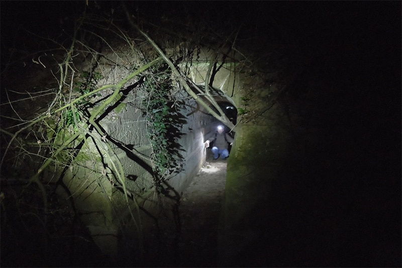 Ein Mann hockt mit einer Stirnlampe in einem dunklem tunnel