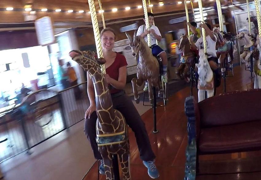 Frau sitzt auf einer Giraffe auf dem Karussel