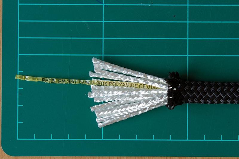 Schwarzes Seil aufgschnitten mit weißen fäden